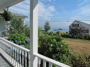 Gaze over rosa rugosa to a lobster boat filled harbor, while rocking on the front porch of Elsa's Inn in Prospect Harbor, Maine. Hilary Nangle photo.