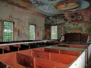 Primitive pews are juxtaposed against contemporary frescoes inside the South Solon Meeting House. Hilary Nangle photo