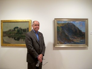 Ogunquit Museum of Art director Ron Crusan stands between The Cliff by Charles Woodbury, and First Bridge, Perkins Cove by Hamilton Easter Field.