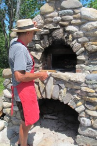 Slideing a pizza into Seal Cove Farm's outdoor oven. Hilary Nangle photo. IMG_3724