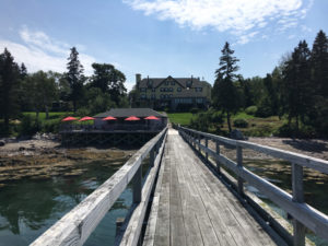 Red umbrellas provide shade so you can enjoy the views over Somes Sound while having lunch at The Boathouse at the Claremont in Southwest Harbor. ©Hilary Nangle